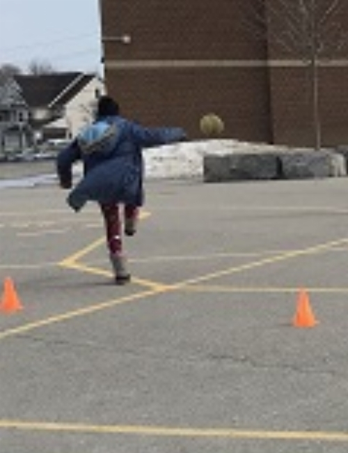 School age child kicking a ball out of their zone