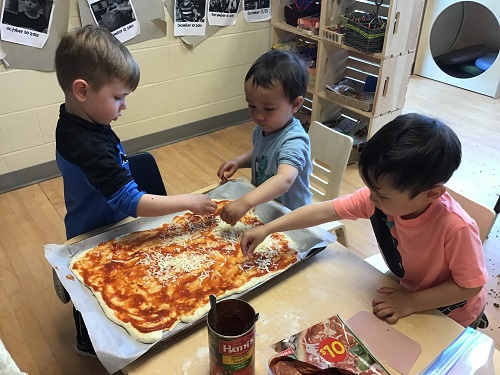 3 boys spreading pizza sauce on pizza