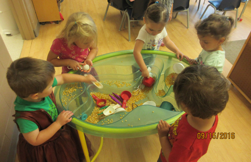 children playing with popcorn seeds in a bin
